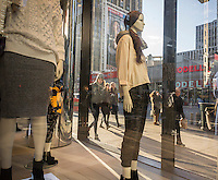 Crowds pass an H&M window display in New York on Thursday, January 22, 2015. (© Richard B. Levine)