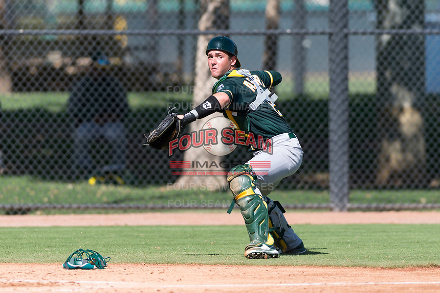 Oakland Athletics catcher Cesare Astorri (12) throws to first base during an Instructional League game against the Los Angeles Dodgers at Camelback Ranch on September 27, 2018 in Glendale, Arizona. (Zachary Lucy/Four Seam Images)