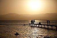 A golden sun drops into the Red Sea at Aqaba, Jordan
