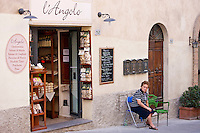 Local woman sitting outside L'Angolo delicatessen food shop in Montalcino, Val D'Orcia,Tuscany, Italy