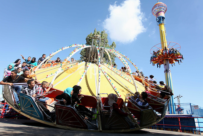 Palestinians enjoy a ride in an amusement park on the second day of Eid al-Fitr, marking the end of Islam's fasting holy month of Ramadan, in the west Bank city of Ramallah on Aug. 09, 2013. Muslims around the world are celebrating Eid al-Fitr this week, marking the end of holiest month of Ramadan during which followers are required to abstain from food, drink and sex from dawn to dusk. Photo by Issam Rimawi