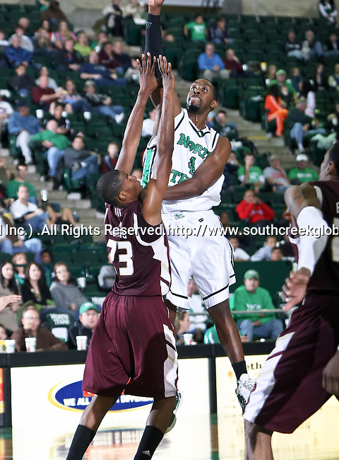 North Texas Mean Green forward George Odufuwa (4) goes up for a jump shot over Texas State Bobcats forward Cameron Johnson (23) in the game between the Texas State Bobcats and the University of North Texas Mean Green at the North Texas Coliseum,the Super Pit, in Denton, Texas. UNT defeated Texas State 85 to 62