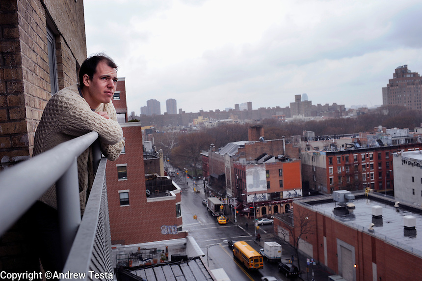 USA. Manhattan . 19th March 2009.Jeffrey Lewis looks out over the city from the balcony of the apartment he grew up in on the lower east side in Mahattan..©Andrew Testa.