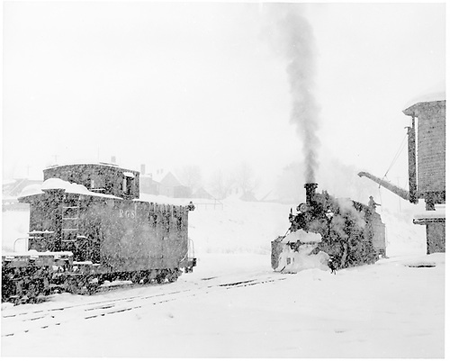 #464 at Durango water tank in snow.  RGS caboose #0404 is on an adjoining track with the RGS consist that #464 will take west and north.<br /> D&amp;RGW  Durango, CO  Taken by Richardson, Robert W. - 12/19/1951