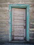 Open, aqua-colored frame door in weathered wooden building, Carlin, Nevada