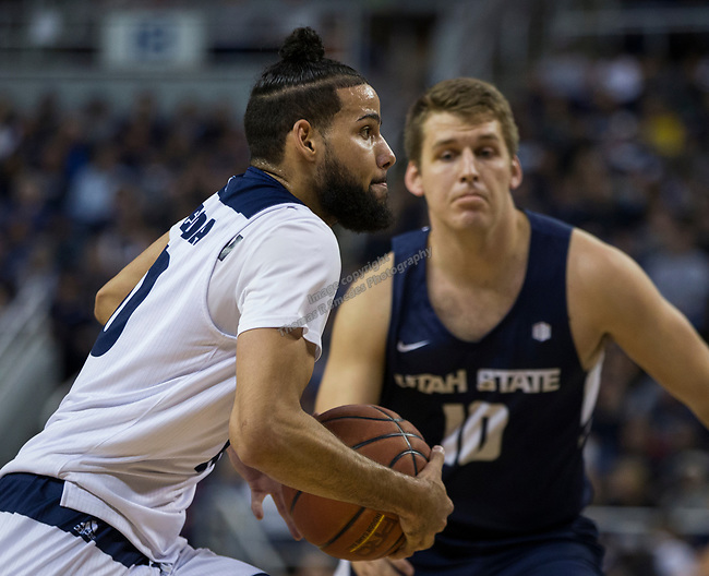 Nevada forward Caleb Martin drives past Utah State center Quinn Taylor (10) in the first half of an NCAA college basketball game in Reno, Nev., Wednesday, Jan. 2, 2019. (AP Photo/Tom R. Smedes)