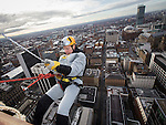 © Joel Goodman - 07973 332324 . 7 December 2013 . Batman ( PAUL SWEENEY , 43 from Worsley - correct ) begins his descent . In scenes reminiscent of a Fathers for Justice demonstration , people in superhero and Christmas-themed costumes , abseil 107 metres down the New York Street side of City Tower to raise money for the Factory Youth Zone in Harpurhey . Photo credit : Joel Goodman