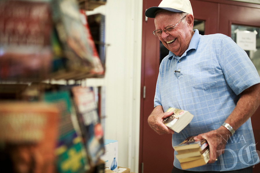 NWA Democrat-Gazette/CHARLIE KAIJO Howard Collins of Little Flock picks out books to buy, Saturday, August 4, 2018 at the Benton County Fairgrounds in Bentonville. <br /><br />Vendors prepared their booths ahead of the Benton County Fair which is set to begin August 7.