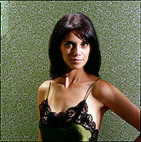 Beauty shot of woman wearing negligee against green patterned wallpaper background<br />