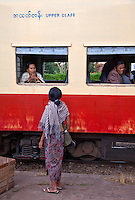 "Myanmar, Burma.  Kalaw Train Station.  ""Upper Class"" Coach Passenger Talking to Woman on Platform."