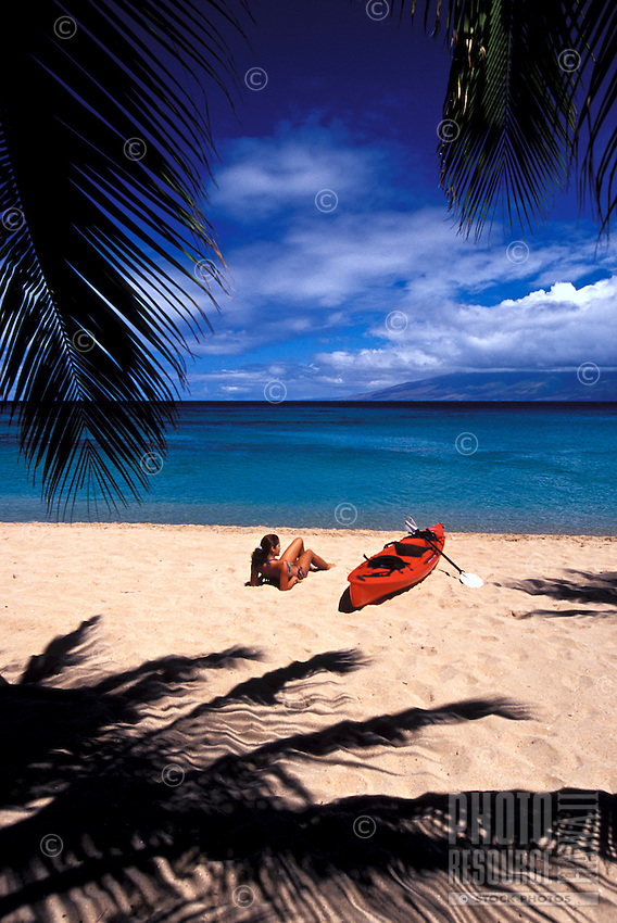 Girl on the beach with red kayak and palm shadows at Napili Bay, Maui.