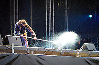 Assistant drying the stage before opening ceremony.