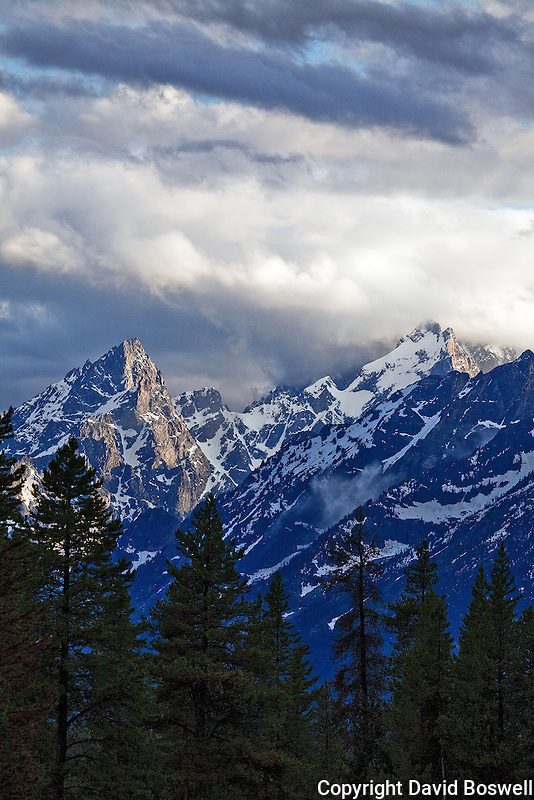 During a summer storm the Tetons are bathed in the light of the setting sun.