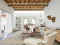 The simplicity of the plain whitewashed walls and concrete flooring allows the subtle tones and textures of the antique furnishings and wooden ceiling to stand out