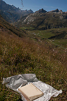 A picnic of Beaufort cheese resting in its wrapper above the Ville des Glacier where the cheese is produced and the cattle graze