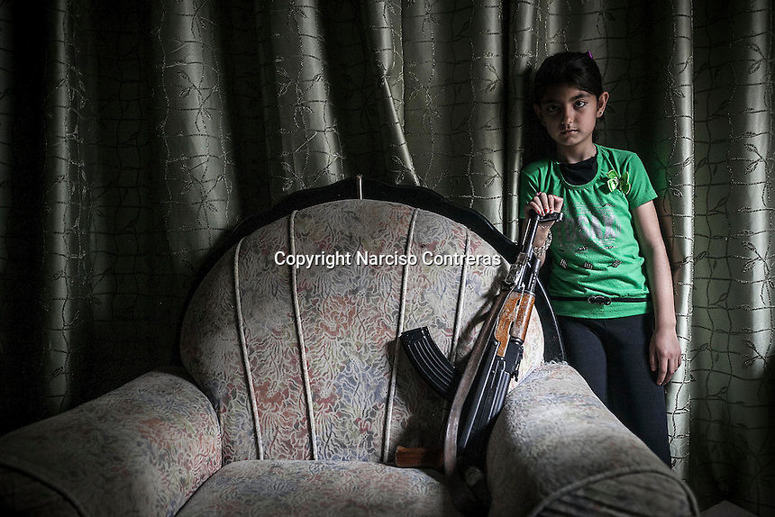 "A Kurdish girl, a female member of the ""Popular Protection Units"" (YPG), stands beside an empty couch as she holds a kalashnikov inside a house in Sheik Maksoud. Her family refuses to leave after Syrian opposition fighters entered into the neighborhood forcing thousands of civilians to flee to safe areas outside of Aleppo City. Since then, the neighborhood is being bombed and shelled by Syrian forces in its attempt to sweep out the opposition fighters from the area. The Kurdish girls, usually at the age of 10, are being trained in combat and guerrilla tactics to become themselves members of the YPG female militias and fight for the Kurdish independency."