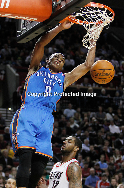 Oklahoma City Thunder point guard Russell Westbrook (0) dunks as Portland Trail Blazers power forward LaMarcus Aldridge (12) defends during third quarter of NBA basketball game in Portland, Oregon,  February 6, 2012.  REUTERS/Steve Dipaola (UNITED STATES)