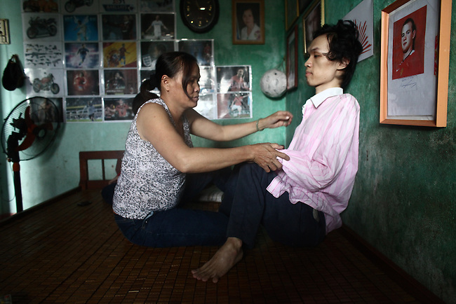 Tran Thi Hoa, 47, cares for her son, 21-year-old La Thanh Toan, at their home in Da Nang, Vietnam. Toan, and his 18-year-old brother Nghia, are third generation victims of dioxin exposure, the result of the U.S. military's use of Agent Orange and other herbicides during the Vietnam War more than 40 years ago. The brothers were born healthy, but began to suffer from muscular dystrophy and other problems as they grew older. They are now confined at home as their bodies and lives waste away. The Vietnam Red Cross estimates that 3 million Vietnamese suffer from illnesses related to dioxin exposure, including at least 150,000 people born with severe birth defects since the end of the war. The U.S. government is paying to clean up dioxin-contaminated soil at the Da Nang airport, which served as a major U.S. base during the conflict. But the U.S. government still denies that dioxin is to blame for widespread health problems in Vietnam and has never provided any money specifically to help the country's Agent Orange victims. Jan. 9, 2013.