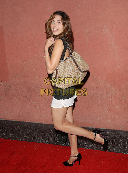 NADINE VALASQUEZ.attends The Hot in Hollywood benefit for The AIDS Healthcare Foundation held at The Henry Fonda Music Box in Hollwyood, California, USA, August 12, 2006..full length black top white mini skirt brown gucci logo bag leg up kicking.Ref: DVS.www.capitalpictures.com.sales@capitalpictures.com.©Debbie VanStory/Capital Pictures