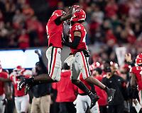ATHENS, GA - NOVEMBER 23: Richard LeCounte #2 and Tyrique McGhee #26 of the Georgia Bulldogs celebrate a big stop during a game between Texas A