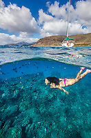 A woman swimming above a reef with a sailboat in background, Electric Beach, West O'ahu