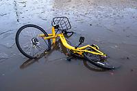 Milano, quartiere Bovisa, periferia nord. Una bicicletta del servizio di bike sharing Ofo vandalizzata, distrutta e abbandonata in una pozza di acqua ghiacciata --- Milan, Bovisa district, north periphery. A bicycle of Ofo bike sharing vandalised, damaged and abandoned in a puddle of frozen water