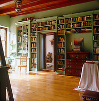 Bookshelves frame the entrance to the green-painted library and have been constructed to accommodate an antique writing desk