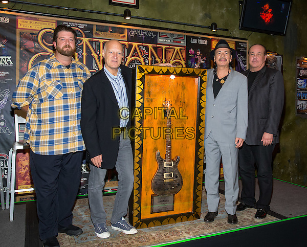 LAS VEGAS, NV - November 3: ***HOUSE COVERAGE*** <br /> Tim Jorgensen, General Manager, House of Blues Las Vegas, Ron Bension, President, House of Blues Entertainment, Carlos Santana and Michael Vrionis, COO, Cristalino pictured as House of Blues executives honor Santana with the a commemorative display marking the sale of his 100,000th ticket to An Intimate Evening with Santana: Greatest Hits Live at House of Blues Las Vegas at Mandalay Bay Resort in Las Vegas, NV on November 3, 2015. <br /> CAP/MPI/EKP<br /> &copy;EKP/MPI/Capital Pictures