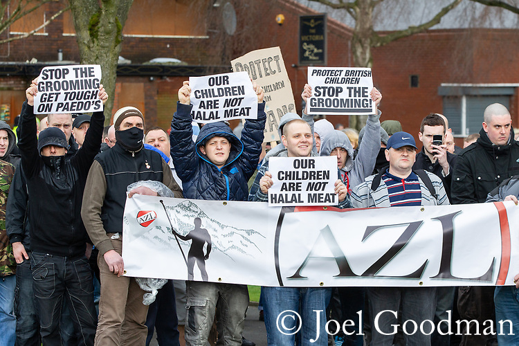 """© Joel Goodman - 07973 332324 . 03/03/2012 . Heywood , UK . Protesters hold an """" Anti Zionist League """" banner and placards reading """" Stop the grooming get touch on paedo's [sic]"""", """" Our children are not halal meat """" and """" Protect british children stop the grooming """" . The National Front hold a rally in protest against an alleged paedophile ring that had been operating in the area . There is currently (3rd March 2012) a case being tried at Liverpool Crown Court in relation to the allegations . Last Thursday (23rd February 2012) a protest organised in the town in relation to the same story resulted in Asian business being attacked by an angry mob . Photo credit : Joel Goodman"""