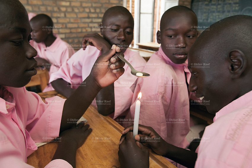 Rwanda. Southern province. District of Muhanga. Central jail of Gitarama. A group of black teenagers boys, wearing the pink prisoner's clothes during the science class. They warm on a candle a ball of naphthalene in a spoon. Bricks wall. Minors block. Minors in detention. Detention pending trial and after trial, sentenced to prison. The non-governmental organization (NGO) Fondation DiDé - Dignité en détention runs the Encademi (Encadrement des mineurs) program. Prison centrale de Gitarama. Quartier des mineurs.  © 2007 Didier Ruef