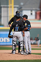 Akron RubberDucks pitching coach Tony Arnold (27) talks with pitcher D.J. Brown (back) and catcher Francisco Mejia (17) during a game against the Erie SeaWolves on August 27, 2017 at UPMC Park in Erie, Pennsylvania.  Akron defeated Erie 6-4.  (Mike Janes/Four Seam Images)