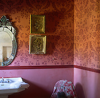 A pink and red bathroom with part patterned wallpapered walls above a dado rail. A venetian mirror hangs above a pedestal washbasin.