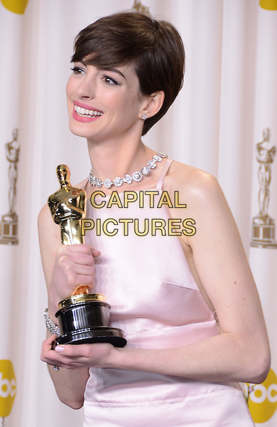Anne Hathaway (wearing Prada).85th Annual Academy Awards held at the Dolby Theatre at Hollywood & Highland Center, Hollywood, California, USA..February 24th, 2013.pressroom oscars half length pink smiling diamonds collar sleeveless silk satin dress award trophy winner .CAP/ADM/RE.©Russ Elliot/AdMedia/Capital Pictures.
