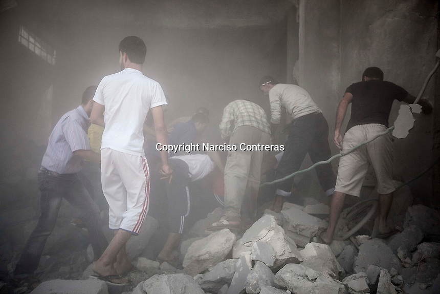 Syrian civilians remove the debris of a demolished house building as they look for the victims of an aircraft shelling just some minutes after the house was targeted by one army plane at Tarik Albab neighborhood in the northeastern of Aleppo City. The Syrian army is carrying out aircraft shellings over residential areas throughout Aleppo City, killing hundreds of civilians in its attempt to sweep out the rebels.