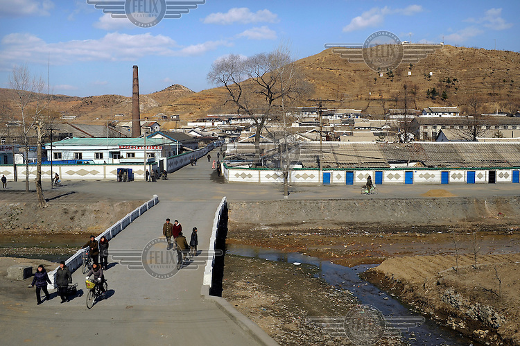 People crossing a bridge in a small town, seen from a train travelling from the Chinese border to Pyongyang.