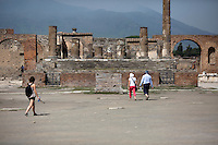 Tourists walk past the Temple of Jupiter on Friday, Sept. 18, 2015, in Pompeii, Italy. The city of Pompeii was destroyed when nearby Mount Vesuvius erupted on August 24, AD 79. The town and its residents were buried and forgotten until the ruins were discovered and eventually excavated hundreds of years later. The ruins are one of Italy's top tourist attractions today. (Photo by James Brosher)