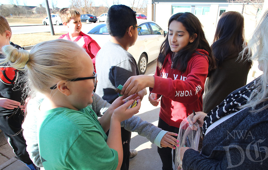 NWA Democrat-Gazette/DAVID GOTTSCHALK  Paige Johnson (left) receives a handful of key chains with the words Do not Text and Drive on them Friday, January 27, 2017, from Nayeli Galvez, both sixth grade students in Another Dimension at Owl Creek School in Fayetteville. The students in the Another Dimension program created the key chains on 3D printers and distributed them to drivers at the as part of a community awareness project. Six printers were purchased through a grant from the Arkansas Education Foundation.
