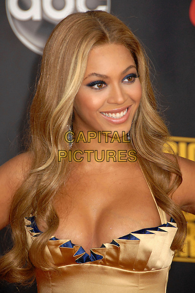BEYONCE KNOWLES.2007 American Music Awards at the Nokia Theatre LA Live, Los Angeles, California, USA..November 18th, 2007.headshot portrait earrings dangling cleavage gold beige blue pleated pleats .CAP/ADM/BP.©Byron Purvis/AdMedia/Capital Pictures.