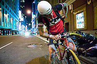 3 July 2005 - New York City, NY, USA - A rider searches for his manifest, at an alleycat checkpoint on 43rd street in New York City, USA, July 3rd 2005. Alleycats are urban cycle races held informally - without notification of the authorities - on open roads and in real traffic, to simulate the messenger's working conditions. Photo Credit: David Brabyn<br />