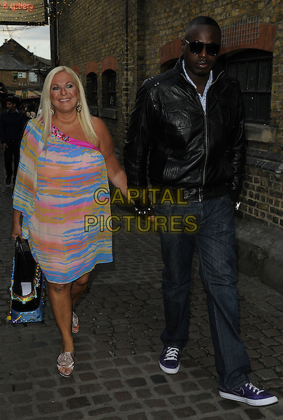 VANESSA FELTZ & BEN OFOEDU.The Beatles: Revolutionary 1965 private view, Proud Camden gallery, Horse Hospital, Stables Market, Chalk Farm Rd., London, England..August 24th, 2011.full length pink blue yellow orange one shoulder dress sleeve jeans denim black leather jacket sunglasses shades holding hands couple .CAP/CAN.©Can Nguyen/Capital Pictures.