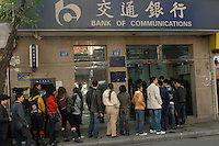 People queue outside a branch of the Bank of Communications in Guangzhou, China..