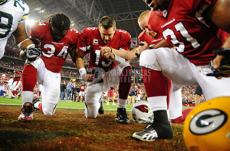 Jan. 10, 2010; Glendale, AZ, USA; Arizona Cardinals quarterback Kurt Warner (13) and running back Tim Hightower (34) pray on the field following the game against the Green Bay Packers in the 2010 NFC wild card playoff game at University of Phoenix Stadium. Arizona defeated Green Bay 51-45 in overtime. Mandatory Credit: Mark J. Rebilas-