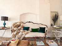 The cream linen upholstered 18th century sofa is covered with rich blue and green velvet cushions and a fur throw
