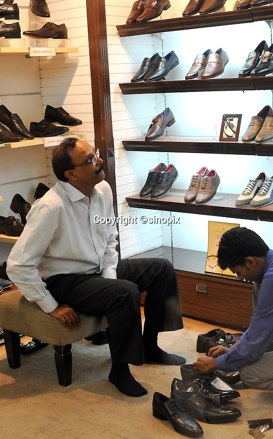 A man tries on shoes at a shoe shop at Express Avenue shopping mall in Madras, India