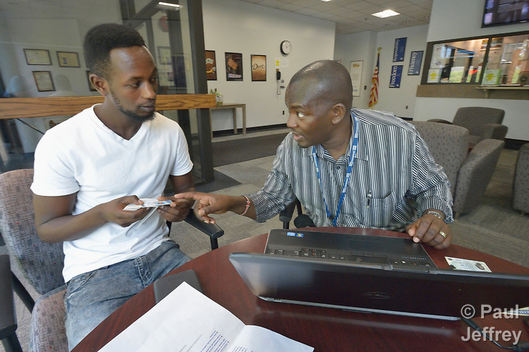 Joseph Shilalo (right), an employment specialist with Church World Service, helps Edson Nsanzubuhoro fill out an online job application at the Mars factory in Elizabethtown, Pennsylvania. Nsanzubuhoro is a newly arrived refugee from the Democratic Republic of the Congo who was resettled in Lancaster, Pennsylvania, by Church World Service.<br /> <br /> Photo by Paul Jeffrey for Church World Service.