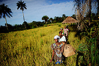 """First in line: Bankapo Kanu, age unknown, is walking through the rice fields of Amdalei village near Lunsar, Sierra Leone. She has born 6 chilren, 3 have not survived. She has never been to a doctor or hospital but takes herbs given to her by the traditional birth attendant, a woman from the village who assists the women during birth. After the last birth, she felt sick for 3 months. Now, she has pains all over her body. """"It is only because of poverty, that I want more children. My body cannot take it anymore."""""""