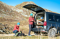 Packing trail running gear and filling water bottles with a hydration powder mix at the car while running the Via Valais, a multi-day trail running tour connecting Verbier and Zermatt, Switzerland