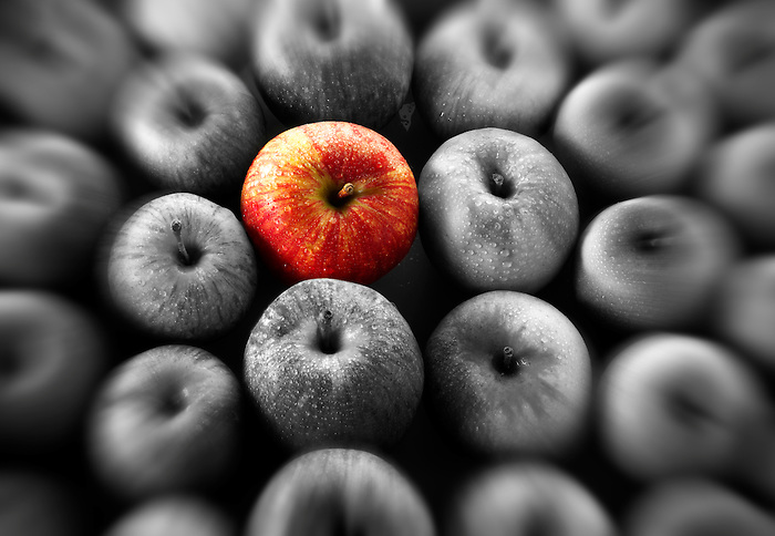 Single red apple amongst other mixed apples