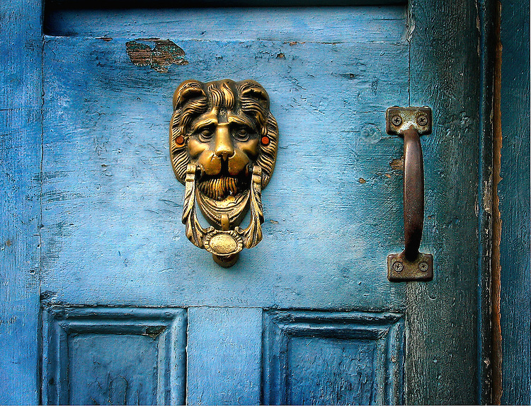 A brass door knocker on a blue door in the shape of a lions head