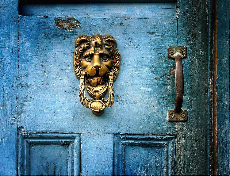 A brass door knocker on a blue door in the shape of a lions head - Antique Door Knocker Trigger Image